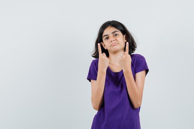 Bambina che indica in su in maglietta e che sembra confusa.