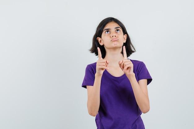 Bambina che indica in su in maglietta e che sembra dubbiosa