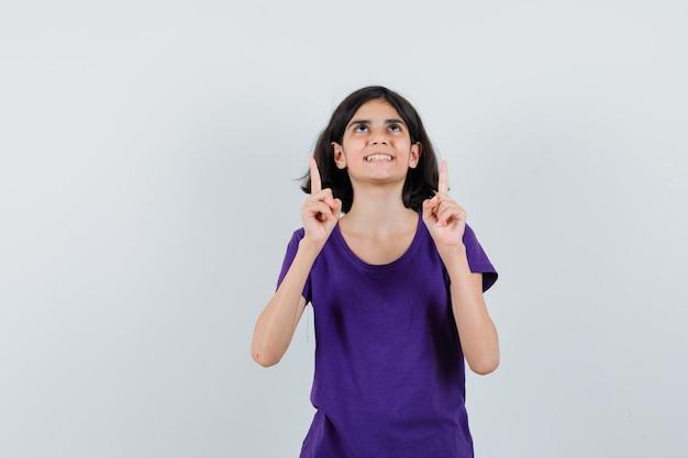 Bambina che indica in su in maglietta e che sembra grata.
