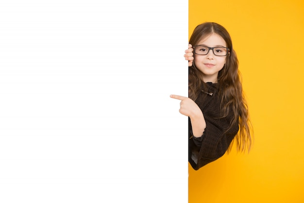 Little girl pointing to white placard background