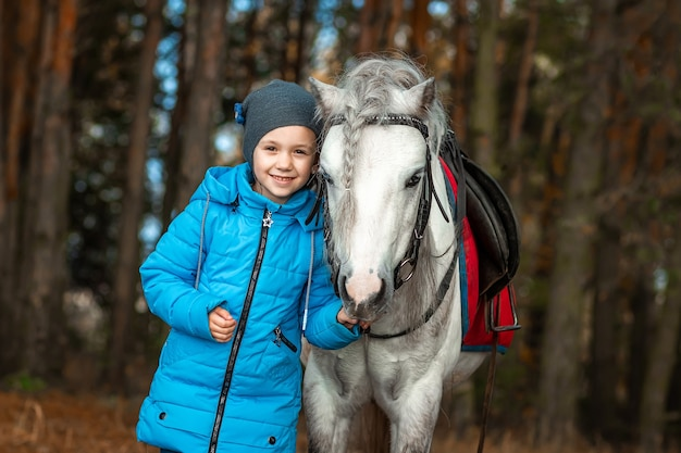 Little girl portrait, stands next to a white pony close-up in nature. jockey, epodrome, horseback riding.