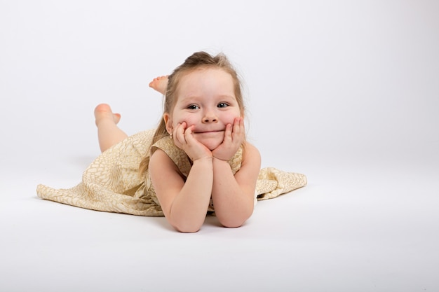 Little girl poses in beautiful dress on grey background