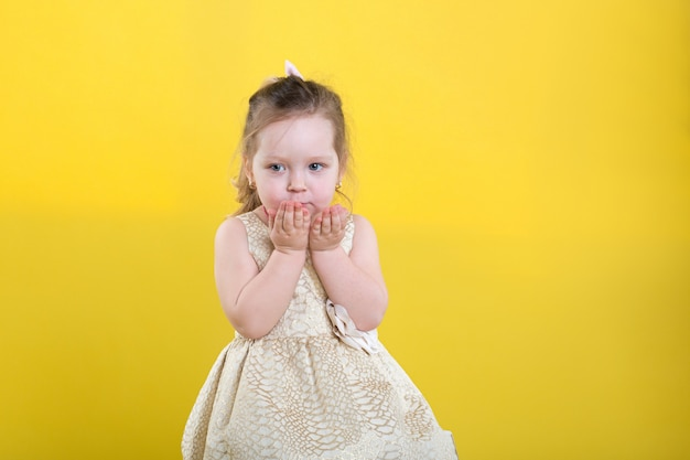 Little girl poses in beautiful dress on yellow background