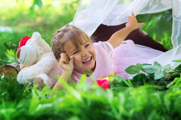 The little girl poses lying outdoors in a tarva and laughs