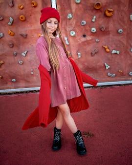 Little girl posing next to a climbing wall