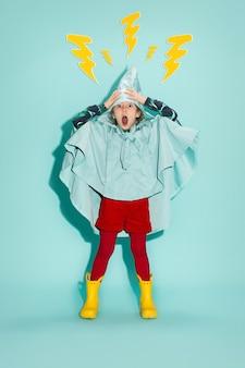 Маленькая девочка позирует в стиле моды в осенней одежде на синем фоне. резиновые желтые сапоги.