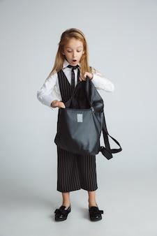 Маленькая девочка позирует в школьной форме с рюкзаком на белой стене