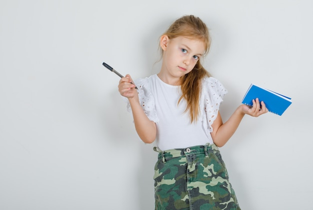 コピーブックとペンを白いtシャツに押しながらポーズの女の子