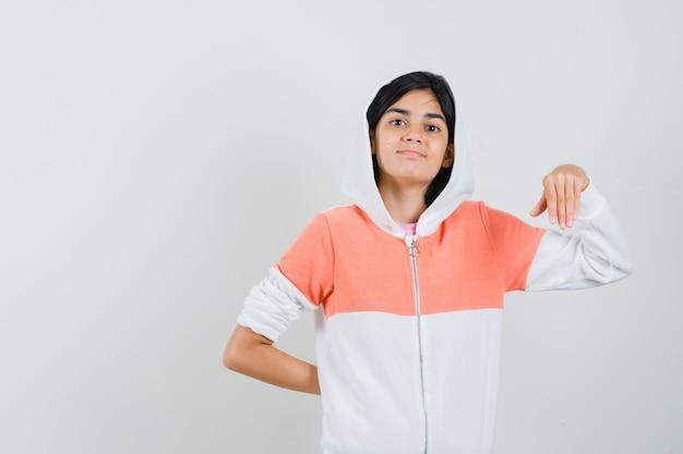 Маленькая девочка позирует, держа руку в футболке, куртке и уверенно.