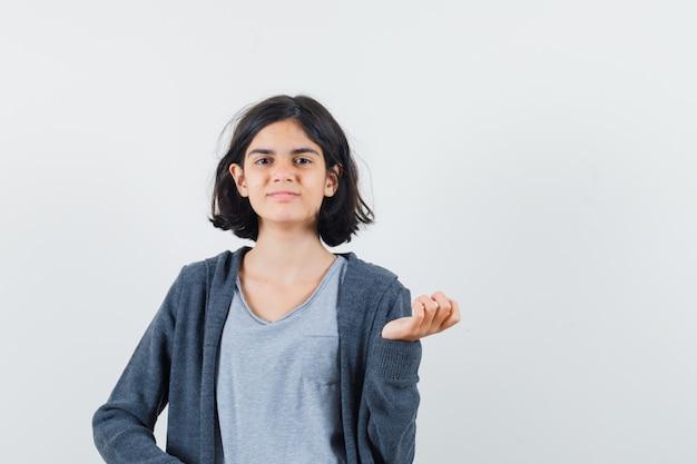 Tシャツ、ジャケットに立って自信を持って、正面図を見てポーズをとる少女。