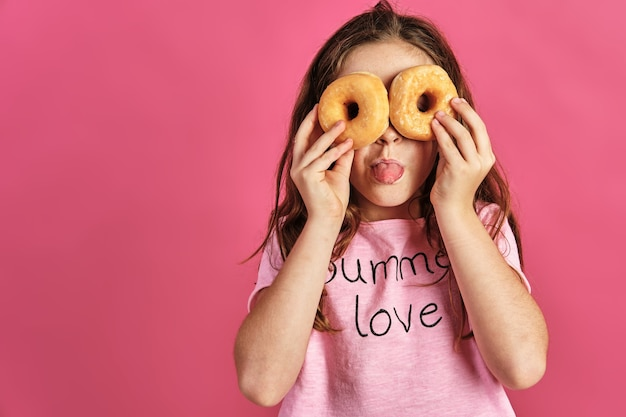 Little girl posing with a couple of donuts on her eyes on a pink wall