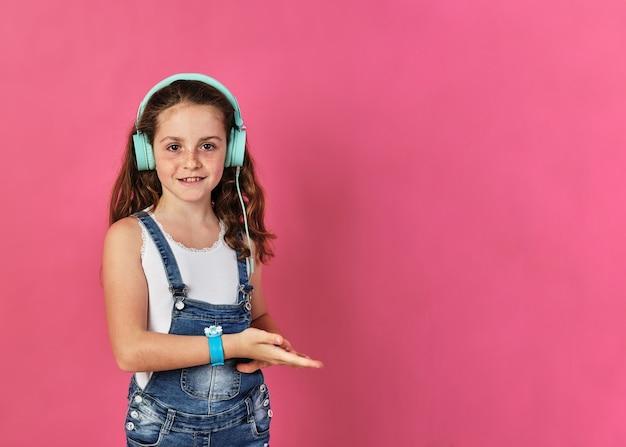 분홍색 벽에 헤드폰을 끼고 포즈를 취하는 어린 소녀