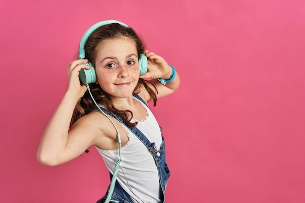 핑크에 헤드폰을 끼고 포즈를 취하는 어린 소녀