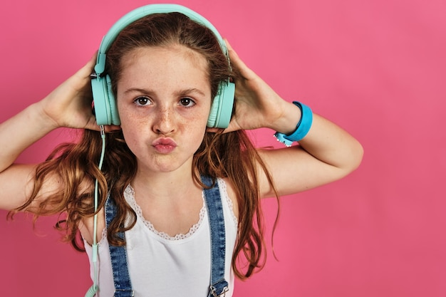 Little girl posing with headphones on a pink wall
