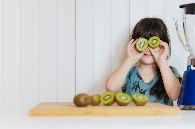 Little girl posing with kiwifruit