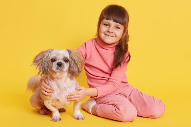 노란색에 북경 강아지와 함께 포즈를 취하는 어린 소녀