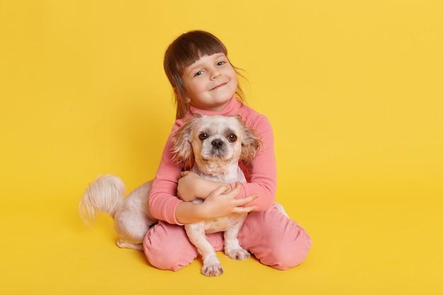 Маленькая девочка позирует с собакой пекинес на желтом
