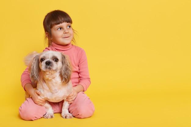 Little girl posing with pekingese dog on yellow