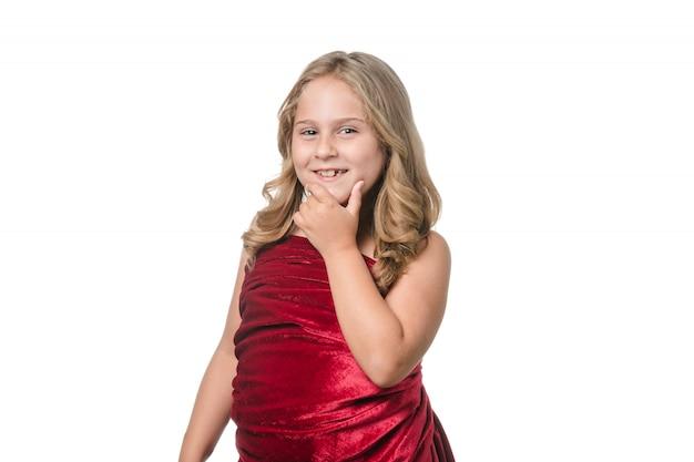 흰색 바탕에 빨간 벨벳 드레스와 함께 포즈를 취하는 소녀 프리미엄 사진