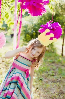 Little girl posing with a toy crown on the children's holiday outdoors