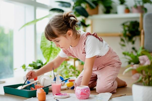 家で小さな女の子のポットの絵