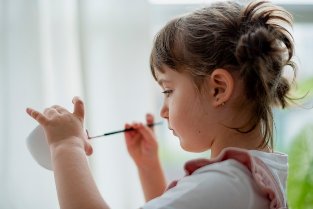 Little girl pot painting at home