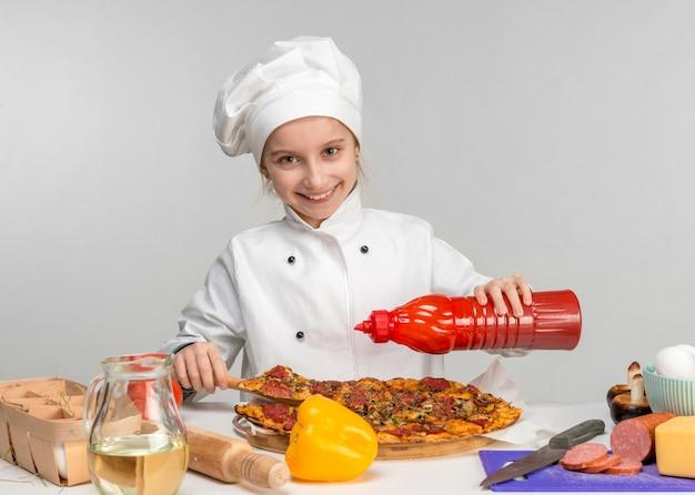 Маленькая девочка налить пиццу с кетчупом