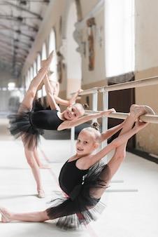 Little girl practicing ballet dance with her friends in dance studio