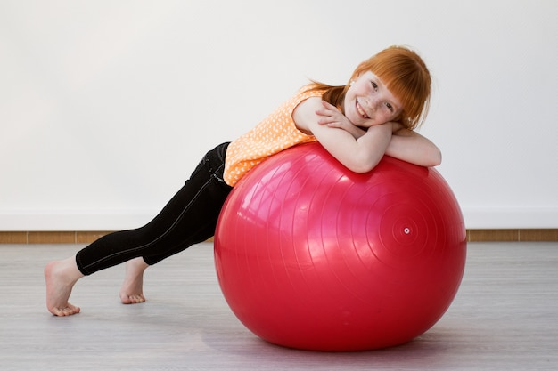 헬스 클럽에서 fitball에 연습하는 어린 소녀