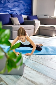 Little girl practicing yoga, stretching, fitness by video on laptop
