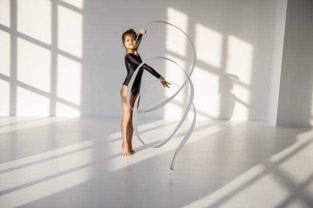 테이프로 리듬 체조를 연습하는 어린 소녀