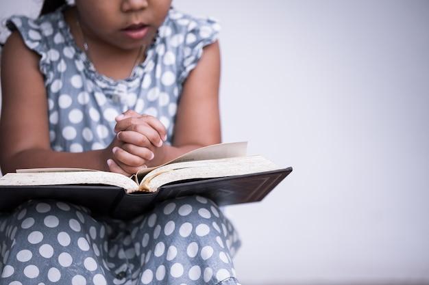 小さな女の子は聖書で祈る