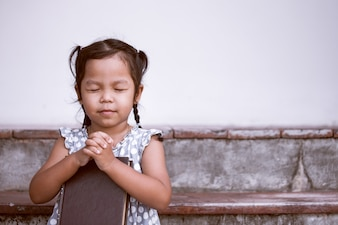 Little girl prays with a holy bible