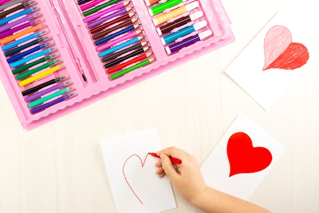 Little girl prepares cards with hearts for valentine's day