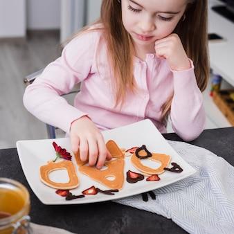 Маленькая девочка готовит завтрак в день отца