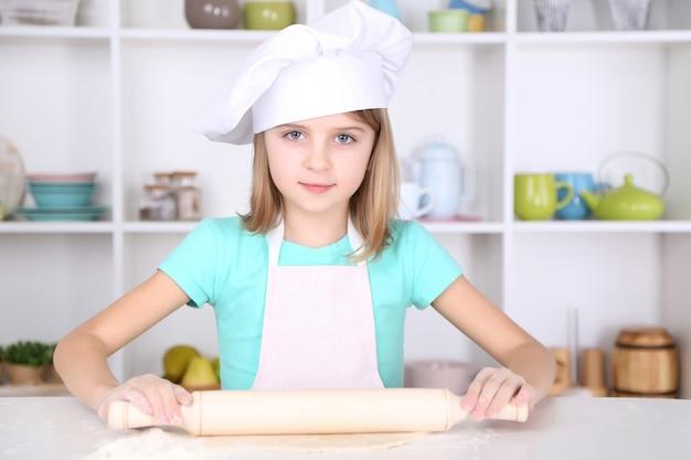 Маленькая девочка готовит тесто для торта на кухне дома