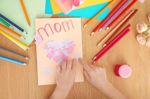テーブルで母の日に彼女のお母さんのためのグリーティングカードを準備している少女