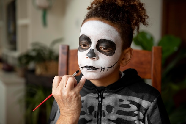 Little girl preparing for halloween with a skeleton costume