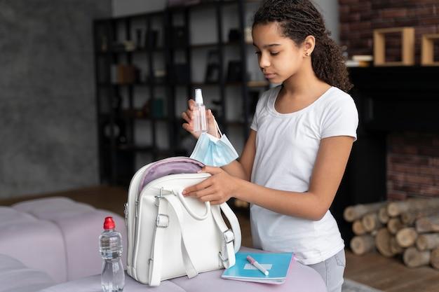 학교로 돌아 가기 위해 그녀의 배낭을 준비하는 어린 소녀