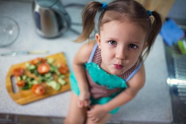 自宅のキッチンでサラダを準備している少女