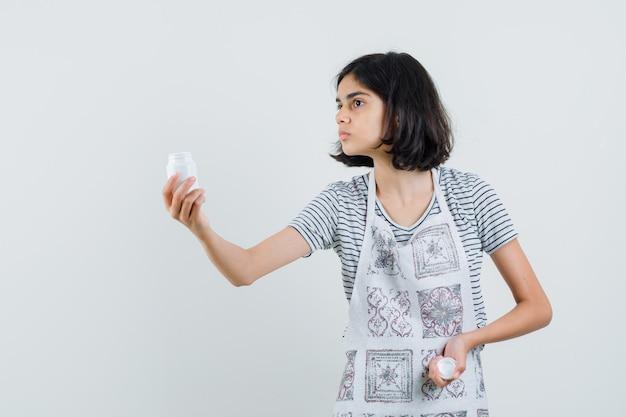 Tシャツの丸薬のボトルを提示する少女