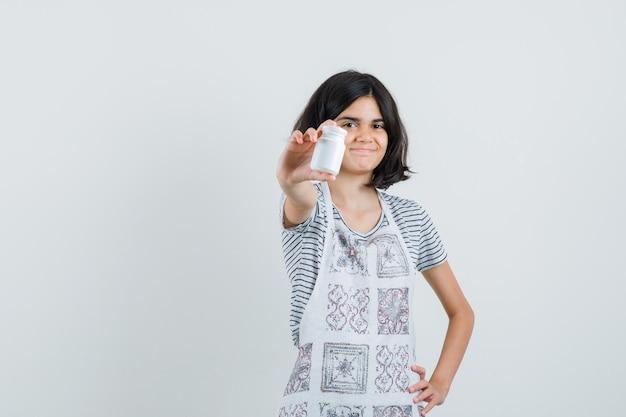 Bambina che presenta una bottiglia di pillole in maglietta, grembiule e guardando fiducioso.