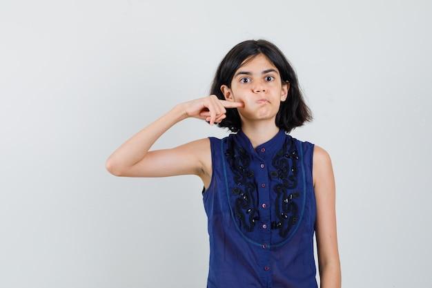 Bambina che preme il dito sulla guancia soffiata in camicetta blu e sembra divertente