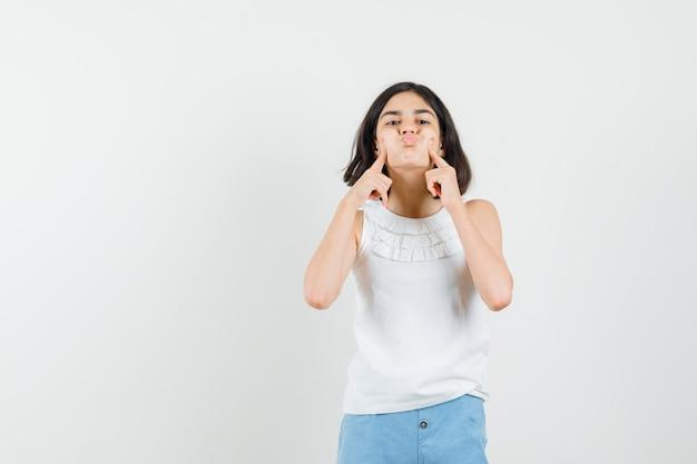 Bambina che preme le dita sulle guance soffiate in camicetta bianca, pantaloncini e sembra carina, vista frontale.