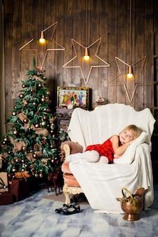 クリスマスツリーの近くの肘掛け椅子で寝ているふりをして、プレゼントを持ってサンタに会う少女。