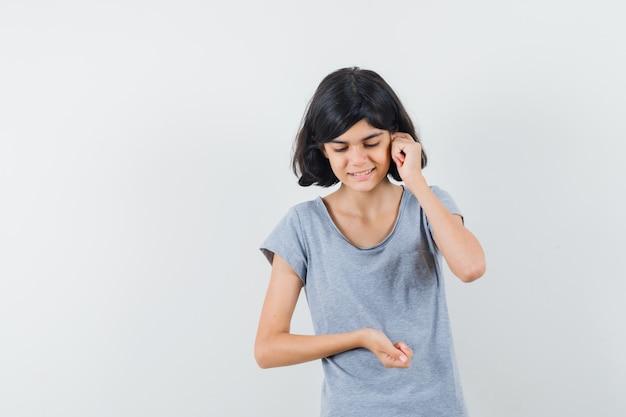 Tシャツを着て携帯電話で話すふりをして物思いにふける少女、正面図。
