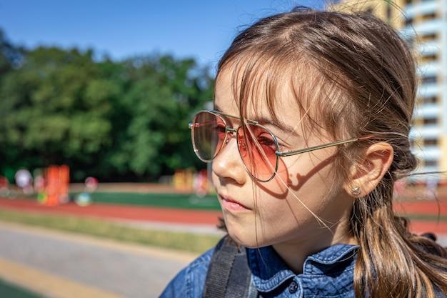 Маленькая девочка, ученица начальной школы в солнечных очках, на открытом воздухе крупным планом.