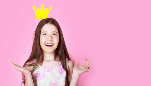 어린 소녀 공주, 왕관, 분홍색 배경에 고립. 아이는 황금 왕관 기호 공주를 착용합니다. 작은 공주님. 소녀는 왕관 분홍색 배경을 착용합니다. 공간을 복사합니다.