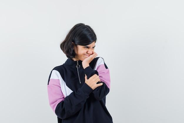 Bambina puntellando il mento a portata di mano in camicia e guardando allegra. vista frontale.