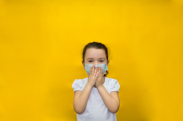 Little girl in a protective mask covers her breath with her hands on a yellow wall. protection against coronavirus